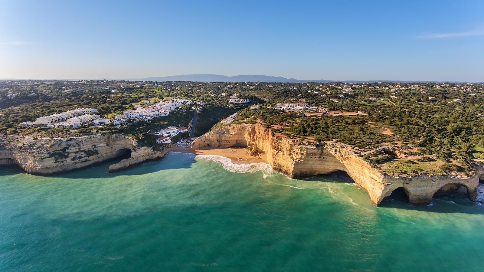 Benagil beach and fishing port is filmed from the sky. Algarve Portugal